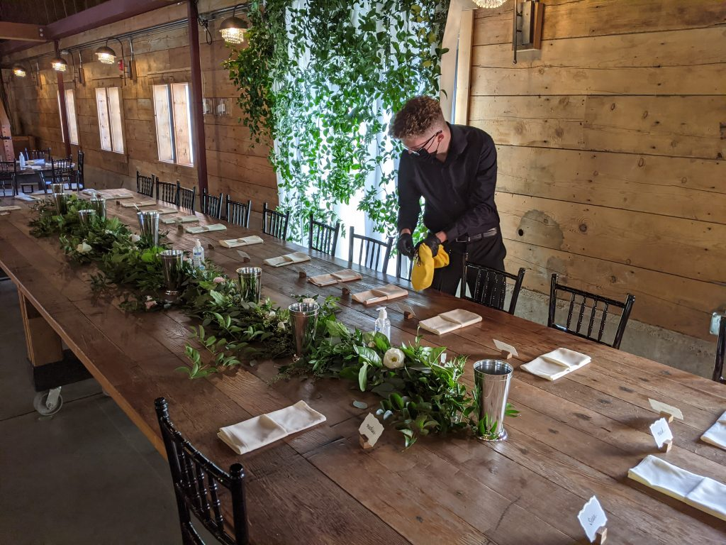 Catering during Covid. An Abritin employee sets out table settings at a wedding during Covid.
