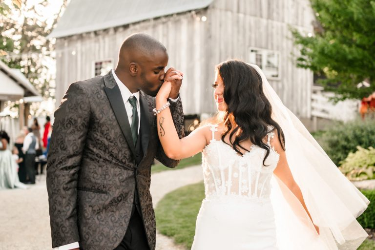 Groom kissing brides hand in front of barn